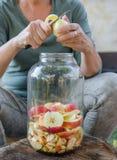 Frau macht Apfelessig - Schalenapfel und schnitt ihn in eine Flasche stockbilder