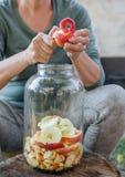 Frau macht Apfelessig - Schalenapfel und schnitt ihn in eine Flasche stockfoto