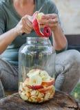Frau macht Apfelessig - Schalenapfel und schnitt ihn in eine Flasche stockfotografie