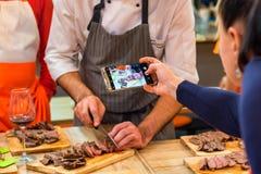 Frau macht das Foto des Chefs Steak schneiden Stockbilder