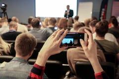 Frau macht ein Foto während der Konferenz unter Verwendung des Smartphone stockbild