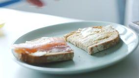 Frau macht einfache Fischsandwiche zum Frühstück stock video