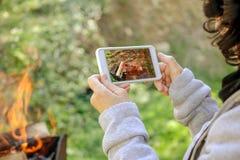 Frau macht Fotos des Feuers auf ihrem Smartphone draußen Lizenzfreie Stockfotos