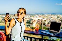 Frau macht selfie in einem Café auf dem Dach eines Wolkenkratzers Mädchen, das mit einem Laptop und einem orange Cocktail an gege stockfotografie