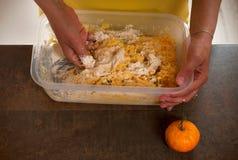 Frau macht Teig f?r Ostern-Kuchen mit getrockneter Rosine, gehackte Mandeln und zerquetschte Mandarinenoberteile ?ber braunem h?l stockfotos