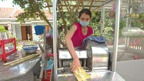Frau macht Zuckerrohr-Saft mit Maschine in der Straße stock video