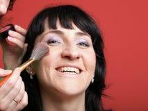 Frau malt Gesicht mit Verfassung Stockfotos