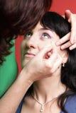 Frau malt Gesicht mit Verfassung Lizenzfreie Stockbilder