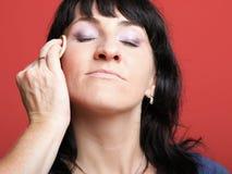 Frau malt Gesicht mit Verfassung Stockbilder