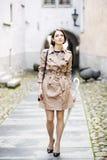 Frau am Mantel mit Handtasche auf heller Straße stockfotografie