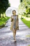 Frau am Mantel mit Regenschirm am sonnigen Tag lizenzfreie stockfotografie
