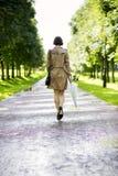 Frau am Mantel mit Regenschirmweg im Park lizenzfreie stockbilder
