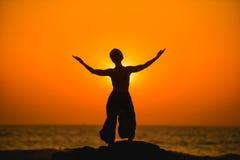 Frau meditiert während des Yoga im Sonnenuntergang Stockbild