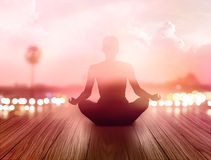 Frau meditierte im Sonnenaufgang und in den Strahlen des Lichtes auf Landschaft Stockbilder