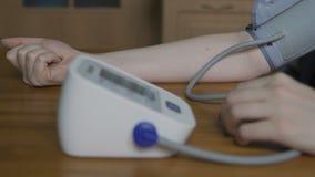 Frau misst ihren Blutdruck stock footage