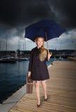 Frau mit altem Koffer und Regenschirm am Hafen Stockbild