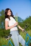 Frau mit altmodischem Fahrrad und Sommerblume Stockbild