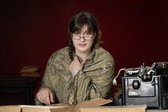Frau mit antiker Schreibmaschine und Büchern Lizenzfreie Stockfotos