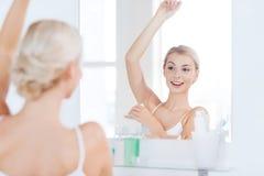 Frau mit Antitranspirationsdesodorierendem mittel am Badezimmer Lizenzfreie Stockbilder