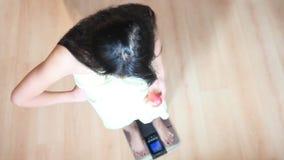 Frau mit Apfel tretend auf Badezimmerwaagen stock video