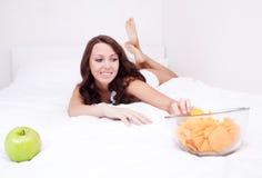 Frau mit Apfel und Chips lizenzfreies stockfoto