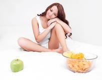 Frau mit Apfel und Chips stockfotos