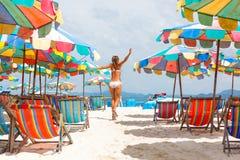 Frau mit Arme angehobenem Betrieb auf Strand Stockfotografie