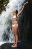 Frau mit Arme angehobener Stellung auf Felsen durch Wasserfall Stockfoto