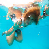 Frau mit Augen öffnen sich unter Wasser im Swimmingpool Stockfotografie