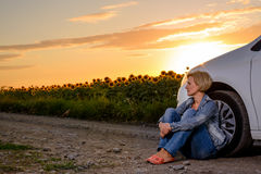Frau mit Auto-Problem im Sonnenblumenfeld Lizenzfreie Stockfotos