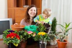 Frau mit Baby mit Blütenpflanzen in den Töpfen Stockbild