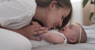 Frau mit Babytochter auf Bett stock video