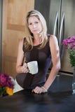 Frau mit Becher in der Küche Stockfoto
