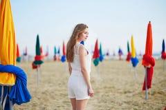 Frau mit berühmten bunten Sonnenschirmen auf Deauville-Strand in Frankreich lizenzfreie stockbilder