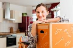 Frau mit beweglichem Kasten in ihrem Haus Stockfotografie