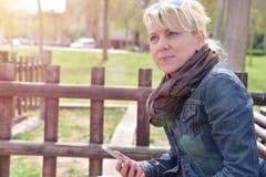 Frau mit beweglichem Sitzen auf einer Bank im Park durchdacht Stockfotos