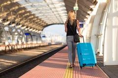 Frau mit blauem Gepäckkoffer gehend auf Bahnstation lizenzfreie stockfotos