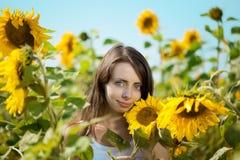 Frau mit blauen Augen mit Sonnenblumen Lizenzfreie Stockbilder