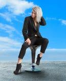 Frau mit blauen Augen sitzt auf Stuhl im schwarzen Anzug Stockfoto