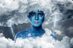 Frau mit blauer Haut in einem Bogen von weißen Wolken Lizenzfreie Stockbilder