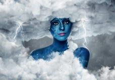 Frau mit blauer Haut in einem Bogen von weißen Wolken Stockfotos