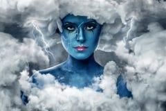Frau mit blauer Haut in einem Bogen von weißen Wolken Lizenzfreie Stockfotografie