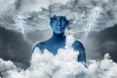 Frau mit blauer Haut in einem Bogen von weißen Wolken Lizenzfreies Stockfoto