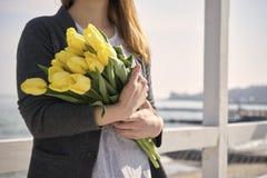 Frau mit Blumen nahe dem Seeufer lizenzfreies stockfoto