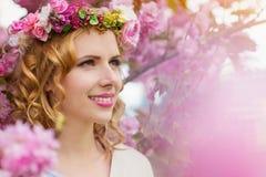 Frau mit Blumenkranz gegen rosa Baum im blossoom Stockfotografie