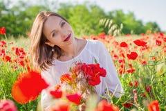 Frau mit Blumenstrauß unter Mohnblumenfeld bei Sonnenuntergang Lizenzfreies Stockfoto