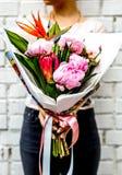 Frau mit Blumenstrauß von Blumen im Kraftpapier Lizenzfreie Stockfotos