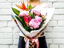 Frau mit Blumenstrauß von Blumen im Kraftpapier Stockbild