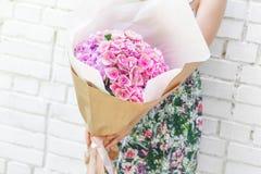 Frau mit Blumenstrauß von Blumen im Kraftpapier Lizenzfreie Stockbilder