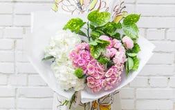 Frau mit Blumenstrauß von Blumen im Kraftpapier Stockfotos